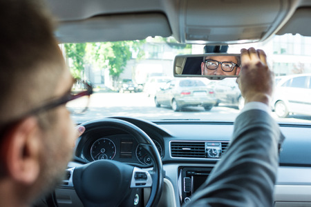 partial view of businessman in eyeglasses looking at rear view mirror in car Banco de Imagens
