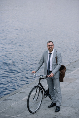 handsome businessman with leather bag standing on quay with bicycle Stock Photo
