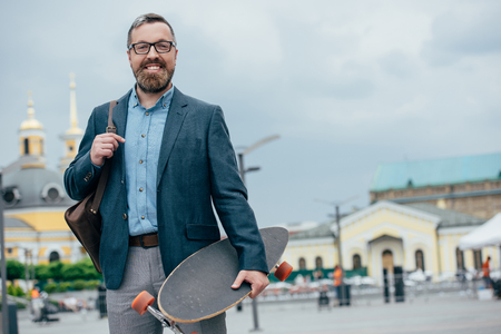 smiling bearded man with leather bag and longboard walking in city
