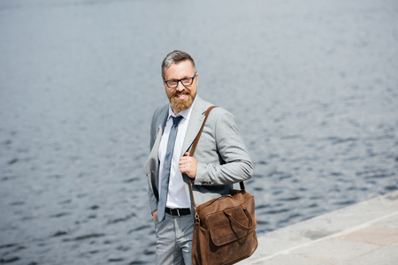 handsome businessman with leather bag walking on quay near river