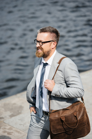handsome bearded businessman in grey suit with leather bag walking on quay Stockfoto