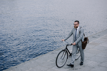 handsome businessman in suit walking with bicycle on quay