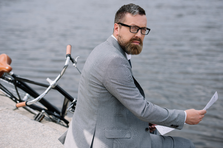 bearded businessman with newspaper sitting on quay with bike Stock Photo