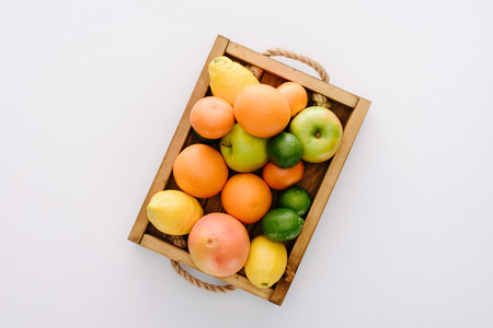 top view of various ripe fruits in wooden box on white tabletop