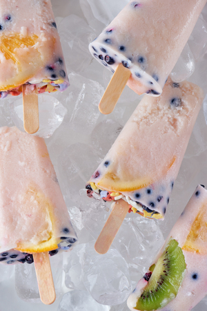close-up view of gourmet homemade ice pop with fruits and berries on ice cubes