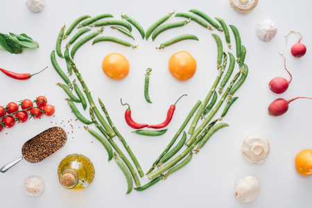 top view of heart made of fresh green peas and asparagus and smiley face from tomatoes and chili peppers isolated on white Stock Photo
