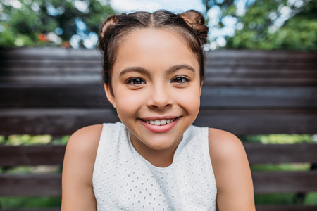 portrait of smiling child looking at camera while sitting on wooden bench Banco de Imagens