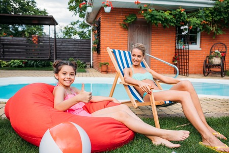 mother and smiling daughter resting near swimming pool on backyard on summer day Фото со стока