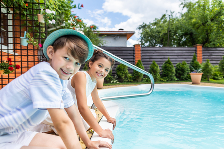 side view of little siblings sitting near swimming pool on summer day