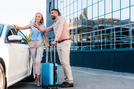 husband and wife with baggage standing at car on parking