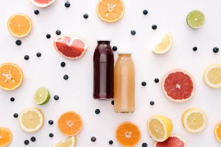 top view of glass bottles of fresh juice with citrus fruits slices on white surface Stok Fotoğraf