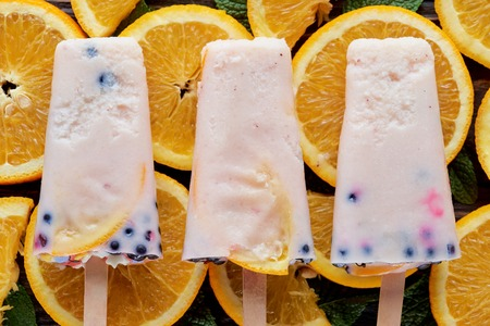 top view of gourmet homemade ice creams pop with fruits and berries on orange slices