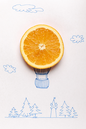 top view of orange slice on balloon flying over forest drawing on white Stock Photo