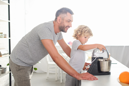 side view of smiling man standing near son while he using mixer for making dough at kitchen Imagens