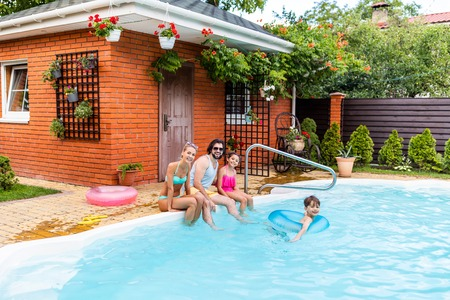 happy family spending time near swimming pool at countryside backyard on summer day Фото со стока