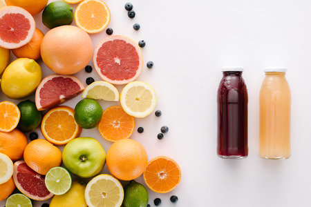 top view of citrus fruits with blueberries and bottle of fresh juice on white surface