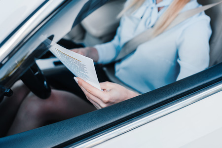 partial view of businesswoman with newspaper on drivers seat in car