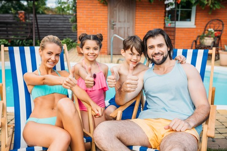 smiling family showing thumbs up while spending time near swimming pool at countryside backyard on summer day Foto de archivo