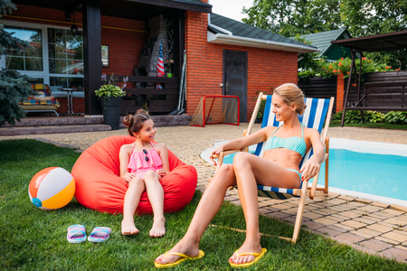 mother and smiling daughter resting near swimming pool on backyard on summer day Stockfoto