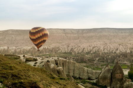 scenic view of hot air balloon flying over stone formations in valley of Cappadocia, Turkey 스톡 콘텐츠
