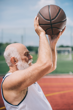 side view of elderly bearded man with basketball ball in hands