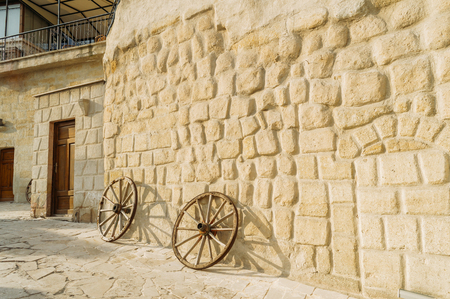 front view of wooden wheels and stone building in Cappadocia, Turkey