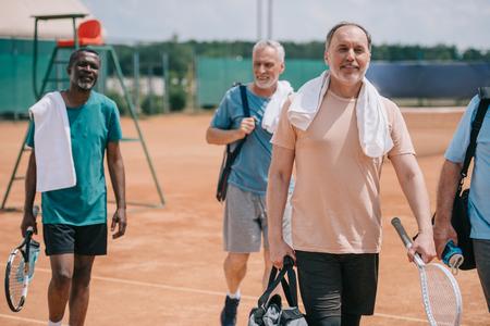 selective focus of multiracial elderly friends with tennis equipment walking on court Foto de archivo