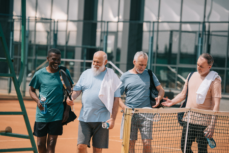 portrait of smiling multiracial elderly friends with tennis equipment on court