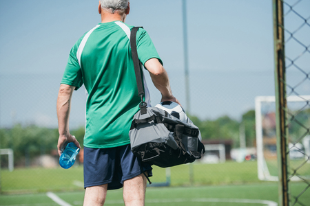 back view of old man with sportive water bottle and bag on soccer field Stockfoto - 105825811