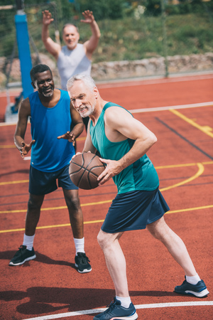 selective focus of old man with basketball ball in hands and multiracial friends behind on playground Stok Fotoğraf