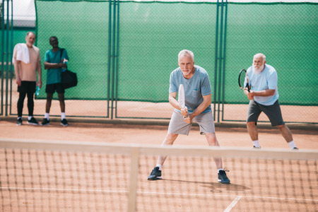 selective focus of old sportsmen playing tennis on court