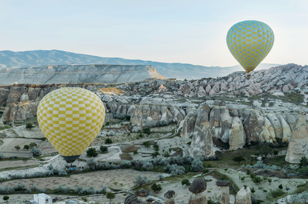 front view of two hot air balloons flying over stone formations in valley of Cappadocia, Turkey 版權商用圖片