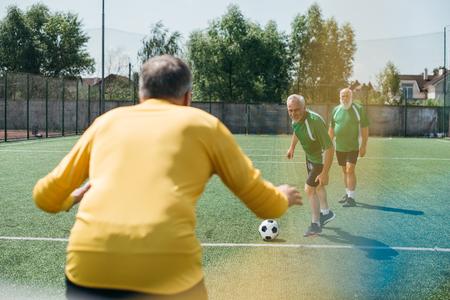 back view of goalkeeper and elderly men on football field
