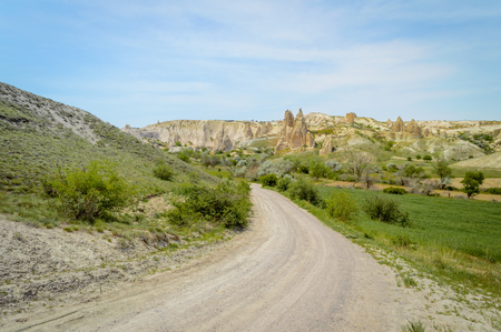 front view of road in valley and mountains under cloudy blue sky, Cappadocia, Turkey