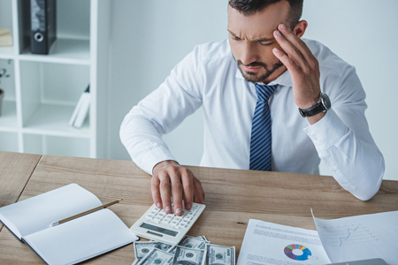 pensive financier counting money with calculator in office and having headache