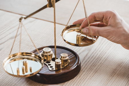 cropped image of financier putting precision weights on scales in office