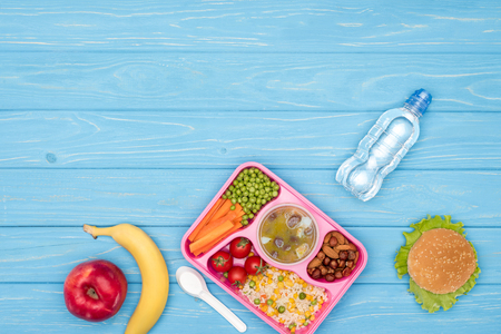 top view of tray with kids lunch for school, bottle of water and fruits on blue wooden surface