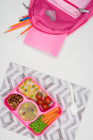 top view of tray with kids lunch for school and pink bag with pencils on white tabletop
