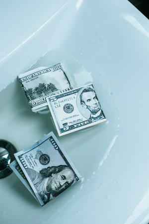 top view of dollar banknotes in water in sink Stock Photo