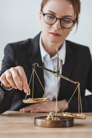 business adviser putting precision weights on scales in office Stock Photo