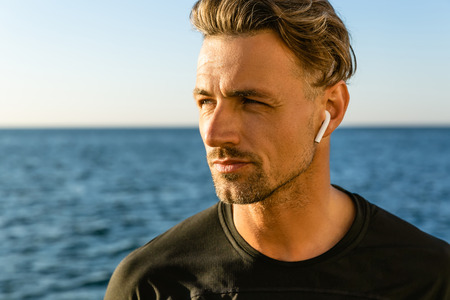 close-up portrait of handsome adult man with wireless earphones on seashore looking away 스톡 콘텐츠