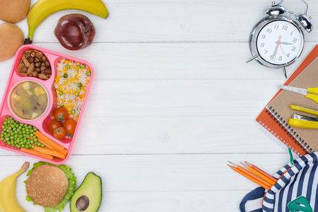 top view of kids lunch for school and alarm clock with bag on wooden table