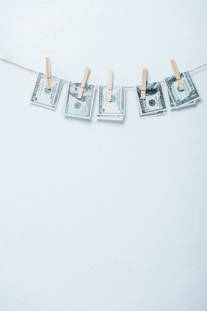dollar banknotes hanging on rope with clothes pins isolated on grey
