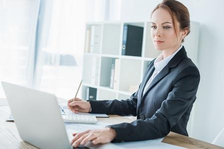 beautiful financier using laptop at table in office