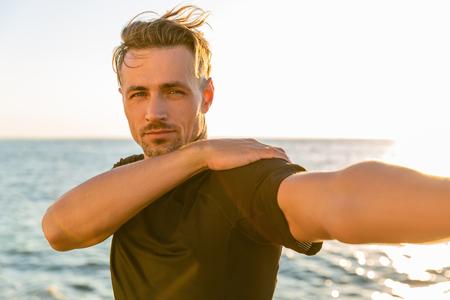 athletic adult man stretching arm before training on seashore