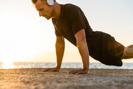 athletic adult man in headphones doing push ups on seashore Stock Photo