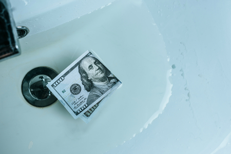 top view of dollar banknote in water in sink Stock Photo