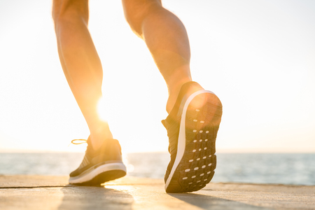 cropped shot of sportsman in modern sneakers running by seashore on senrise Stock Photo