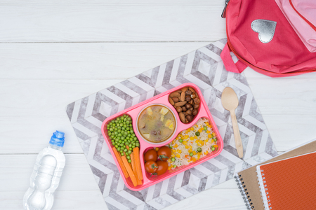 top view of tray with kids lunch for school and copybooks on white tabletop