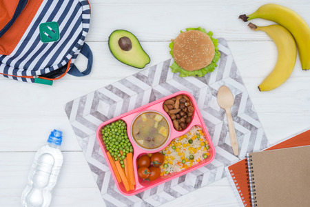 top view of tray with kids lunch for school and copybooks on wooden table